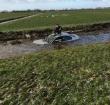 Auto te water, bestuurder op dak